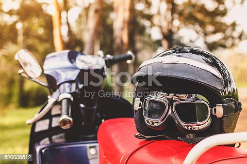 Retro motorcycle helmet with glasses on old scooter