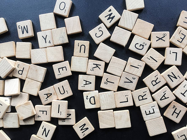 Old Scrabble Tile Letters in Abstract Pile stock photo