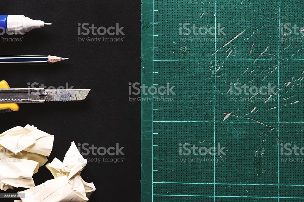 Old scratch cutting mat with cutter,pencil, crumpled paper ball stock photo