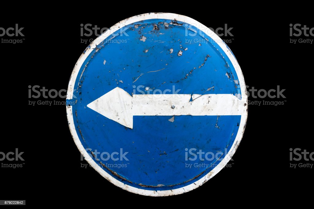 Old scratched round blue road sign 'Turn Left' isolated on black. stock photo