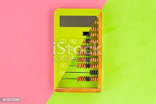 Old scratched wooden brown abacus combined with new green plastic solar calculator on doublecolor paper green and pink color. Top view