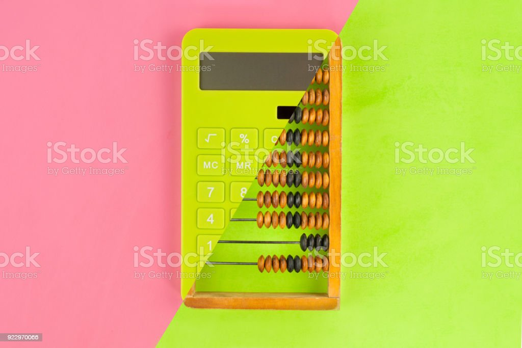Old scratched wooden brown abacus combined with new green plastic solar calculator on doublecolor paper green and pink color. Top view stock photo