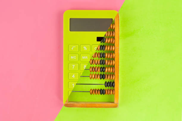 Old scratched wooden brown abacus combined with new green plastic solar calculator on doublecolor paper green and pink color. Top view Old scratched wooden brown abacus combined with new green plastic solar calculator on doublecolor paper green and pink color. Top view abacus stock pictures, royalty-free photos & images