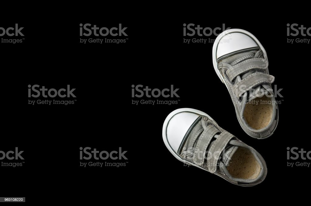 old secondhand black canvas shoes or sneakers for kids or baby and child foot on black background top view with copyspace isolated included clipping path stock photo