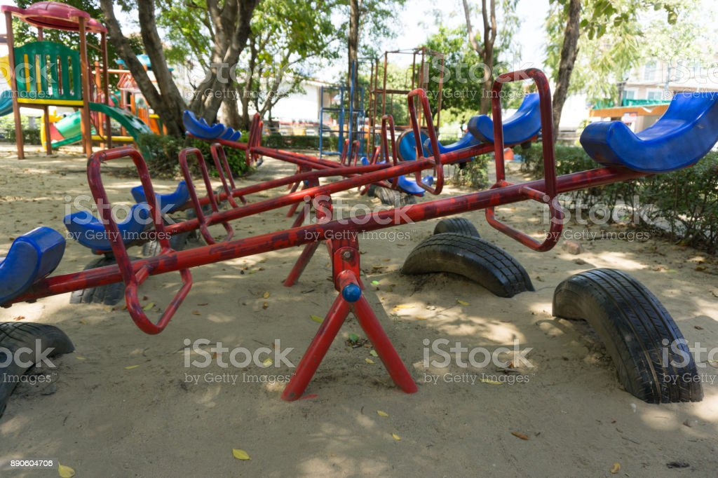 Old seesaw in outdoor playground for kids stock photo