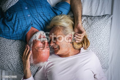 154918758 istock photo Old senior couple are kissing in bed 1159421845
