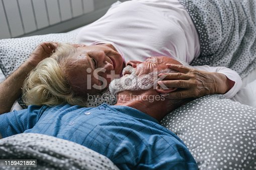 154918758 istock photo Old senior couple are kissing in bed 1159421892