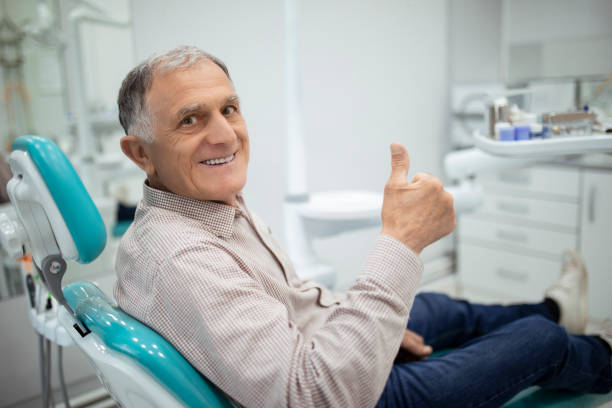 Old senior man sitting in a dental chair Old senior man sitting in a dental chair thumb up only senior men stock pictures, royalty-free photos & images