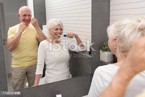 istock Old senior people cleaning teeth in the bathroom 1145251638