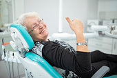 Old senior woman sitting in a dental chair thumb up