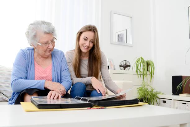 old senior woman with young granddaughter at home looking souvenir - senior fotoboek stockfoto's en -beelden