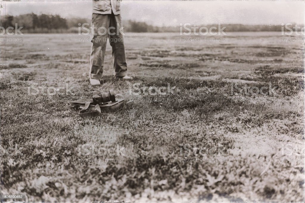 Old sepia photo of leather bag with gloves and camera lying in field. Legs of man in background. stock photo