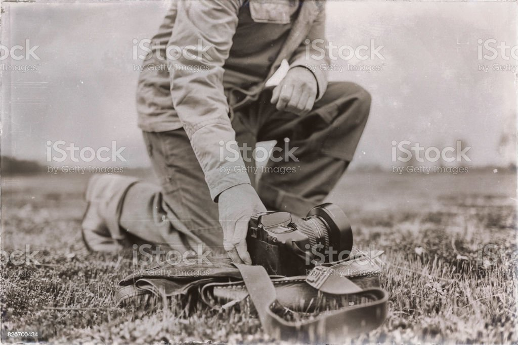 Old sepia photo of nature photographer in field picking up camera. stock photo