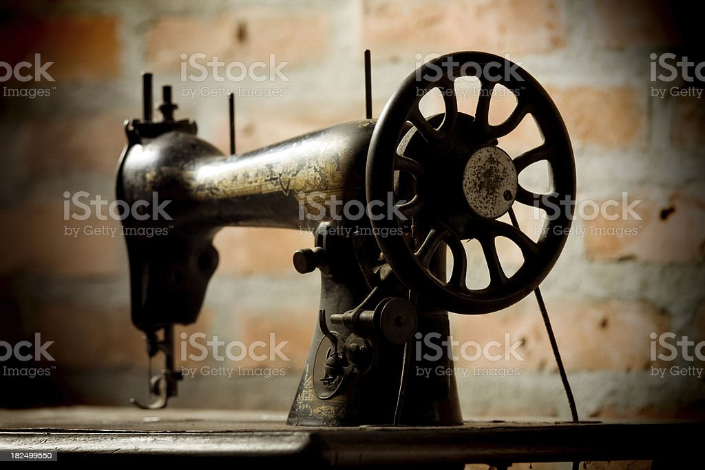 Old sewing machine in front of brick wall. Toned image stock photo