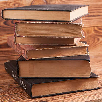 Old shabby books lying on a wooden surface