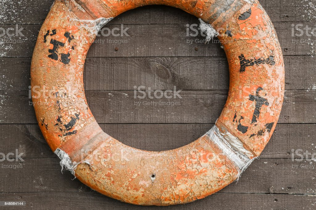 Old shabby life ring attached to the wooden wall. Nostalgia.. it rescued a lot of lives maybe. Rescue concept. stock photo