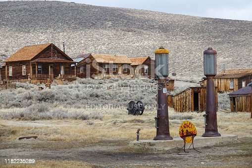BODIE, UNITED STATES, MARCH 2017: Old shell gas station decaying in the middle of an abandoned mining town in America. Rusty remnants of oil pump and abandoned houses weathering the harsh weather.