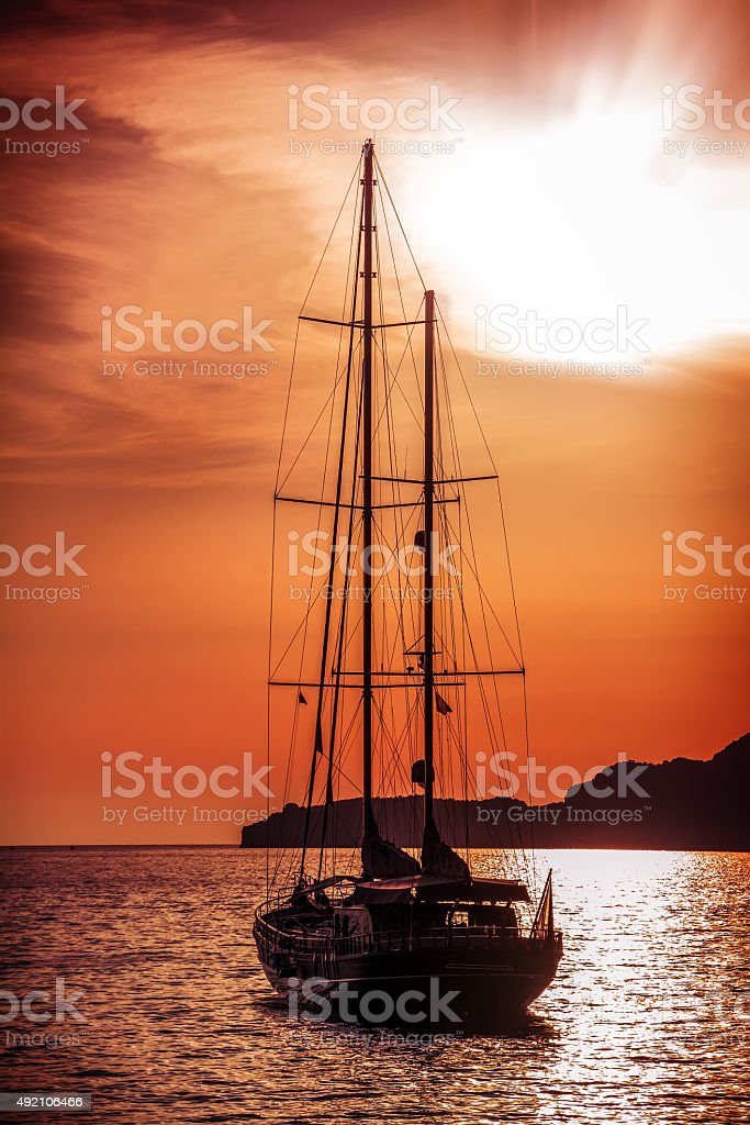 Old ship sailing to the sunset. stock photo