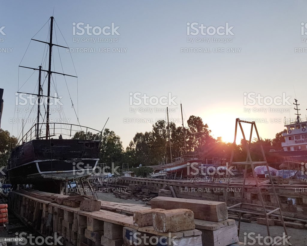 İzmir, Turkey - august 30, 2017: old ships are repaired at docks sunset stock photo