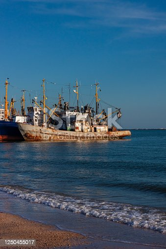 Old ships at the pier on the sea with an empty beach with clear blue sky. Deserted seaport on the shore with cranes and boats. Wallpaper for desktop, poster, marine travel photo for post card design.