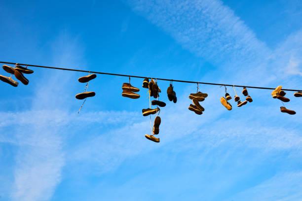 alte schuhe hängen am elektrischen draht gegen einen himmel - kabelschuhe stock-fotos und bilder