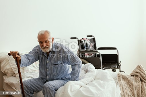 istock Old sick man with grey beard and hair wearing blue pajamas and sitting on bed at home 1131834520