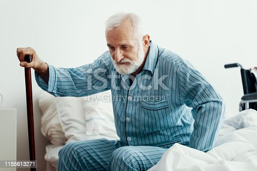 istock Old sick man with grey beard and hair wearing blue pajamas and sitting on bed at home 1155613271