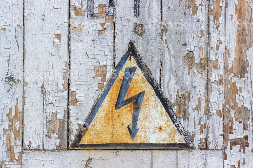 Velho sinal perigo alta voltagem no contexto das velhas tábuas de madeira. - foto de acervo