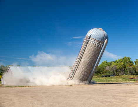 Part of a series of an old silo demolition. In this image, the silo is about one third of the way down. There are other other images in this series showing the complete process.