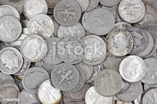 Old silver dimes on a white background.