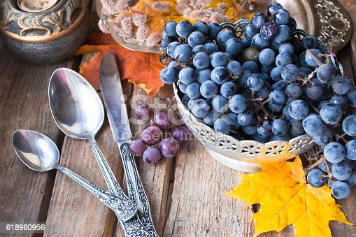 619246768 istock photo Old silver dish with grapes, spoons, autumn leaves on wood 618960956