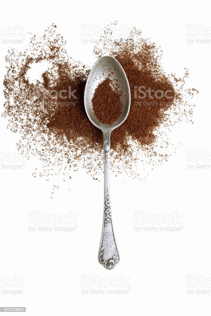 Old silver spoon with ground coffee on a white background. stock photo