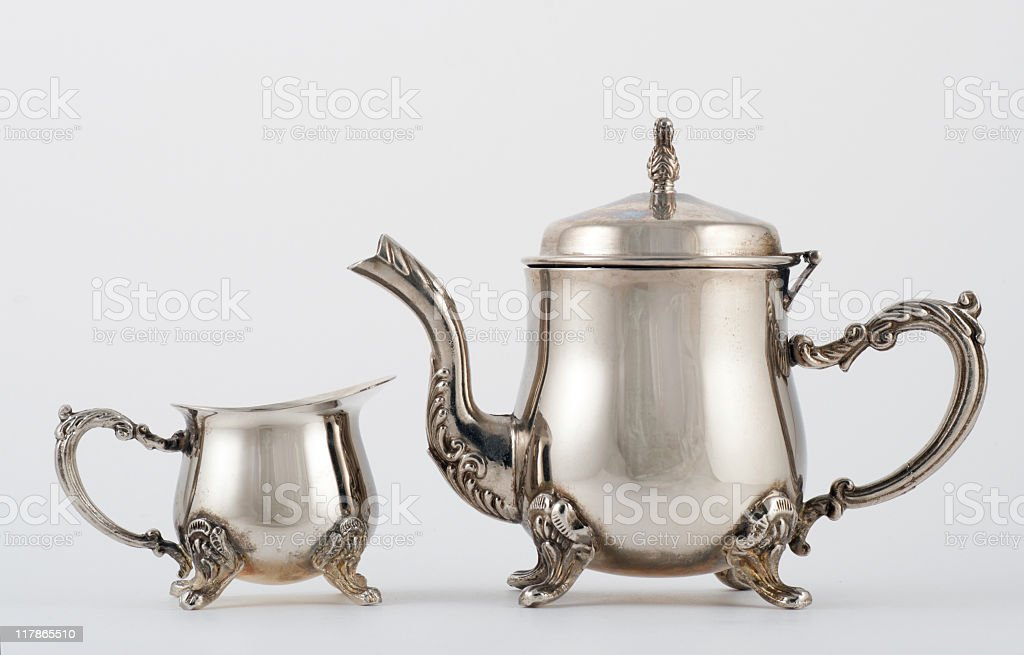 Old silver tea pot and creamer pitcher on white background stock photo