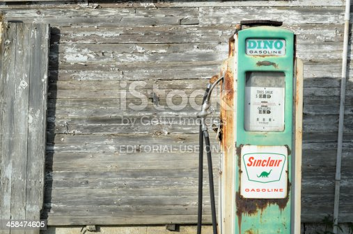 Bedford, Pennsylvania, USA - August 18, 2013: Antique Sinclair gas pump against an old weathered white farm building in rural Pennsylvania, PA, USA.