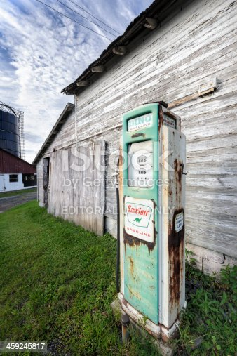Bedford, Pennsylvania, USA - August 18, 2013: Weathered Sinclair gas pump against an old white clapboard farm building in rural Pennsylvania, PA, USA.