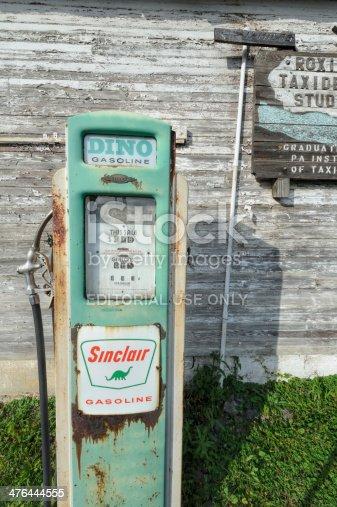 Bedford, Pennsylvania, USA - August 18, 2013: Sinclair gas pump against vintage wooden farm building in rural America.