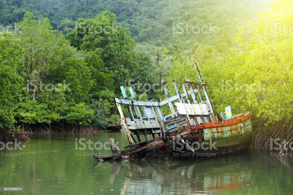 Old Sink fishing boat dock dead along mangrove canal river forest jungle stock photo