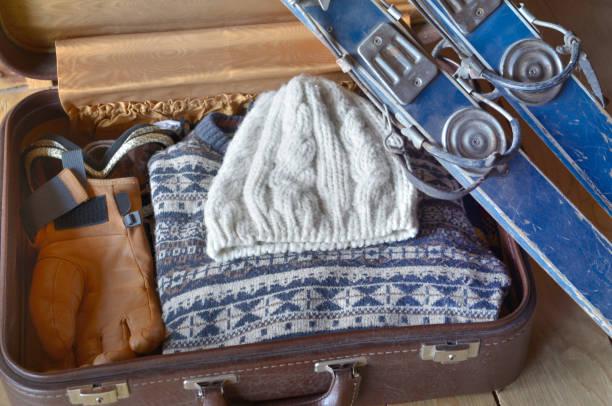 esquí viejo contra una apertura de maleta con ropa de abrigo - foto de stock