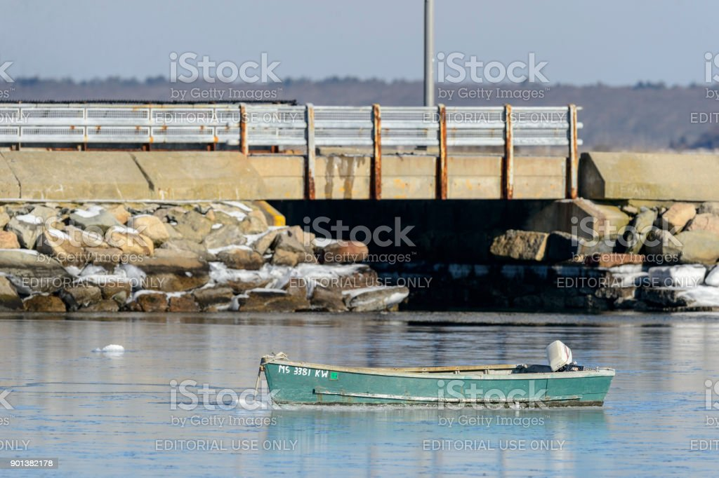 Old skiff on icy bay stock photo