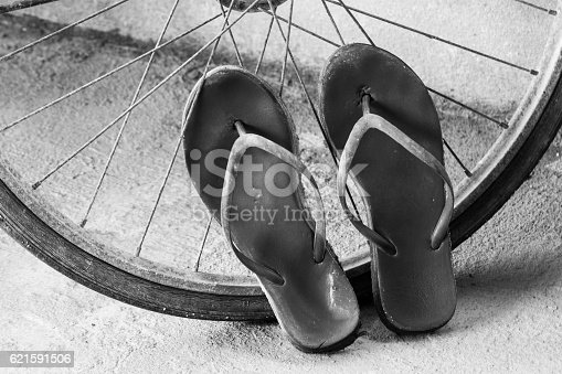 Old slippers and bicycle wheel in black and white tone