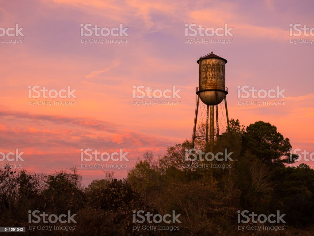 Old Small Town Water Tower Against Brilliant Sunset Sky stock photo