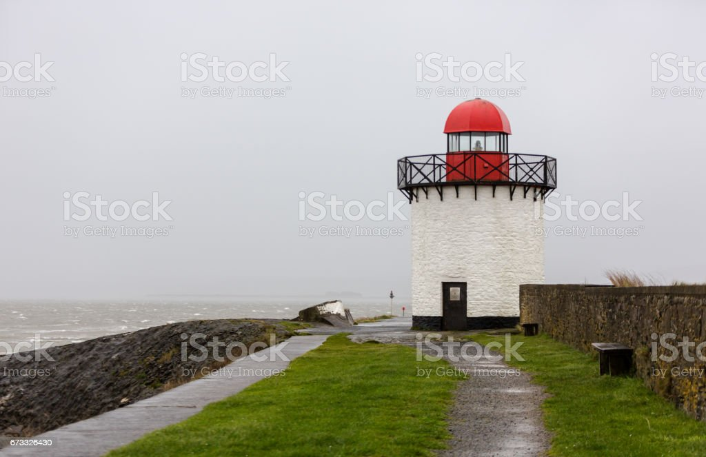 Old small white lighthouse in Burry Port Harbour in bad storm windy weather stock photo