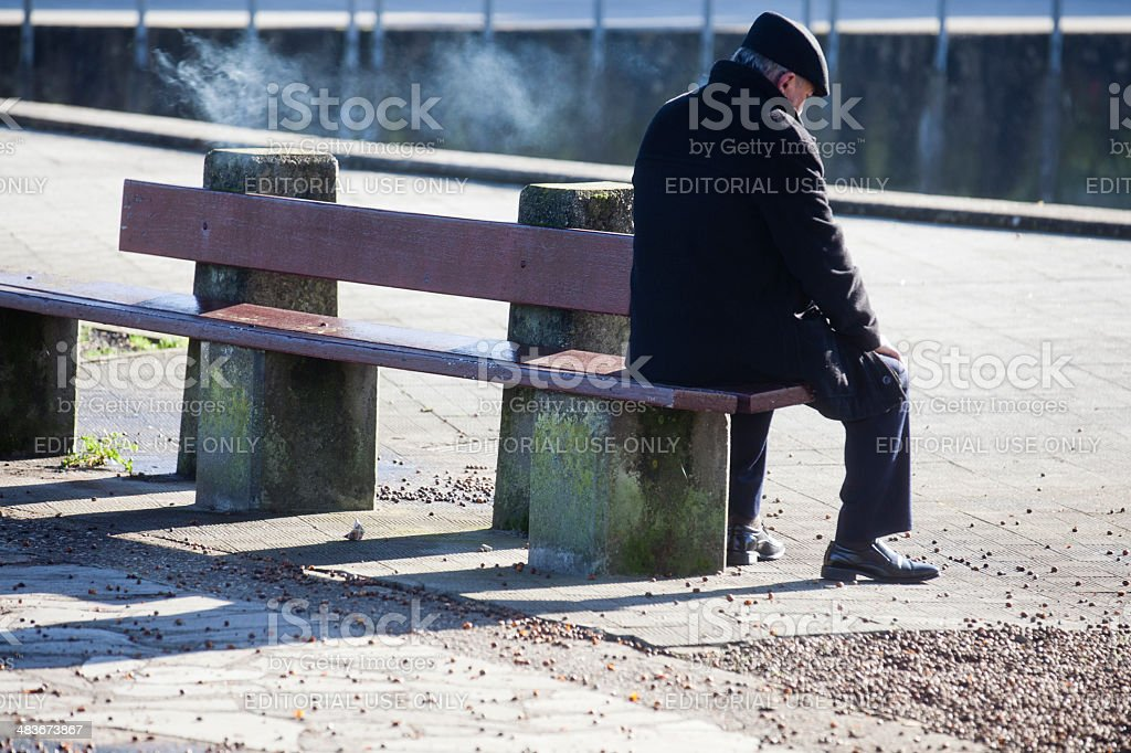 Old smoking man on a bench stock photo