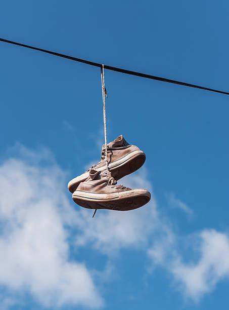 alten sneaker auf einem draht - kabelschuhe stock-fotos und bilder