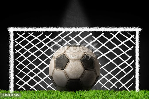 Old leather soccer ball on the green grass with a blackboard on the background with a chalk drawing of a football goal