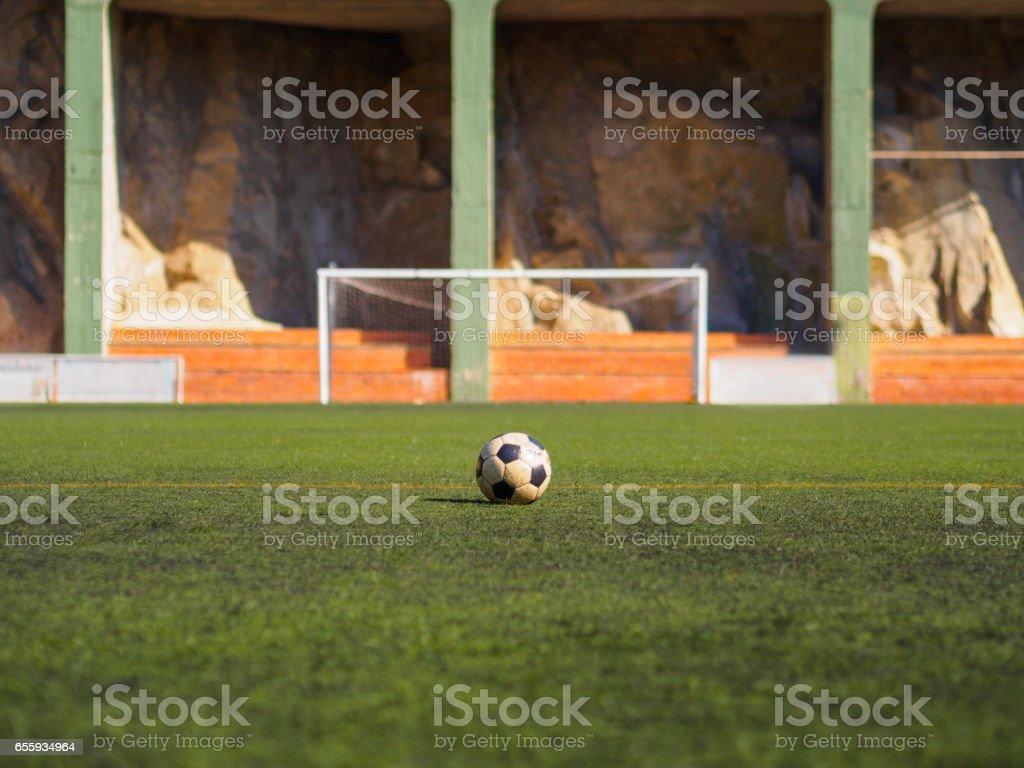Bola de futebol velho deitado no campo de grama, à espera de ser filmado - foto de acervo
