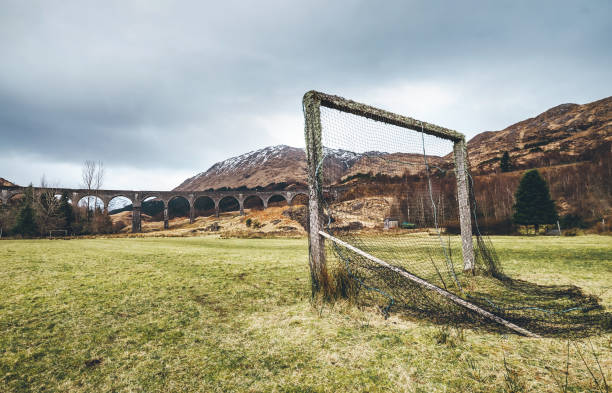 old soccer gate on the green grass playground near the famous glenfinnan viaduct in scotland, united kingdom. - principe harry foto e immagini stock