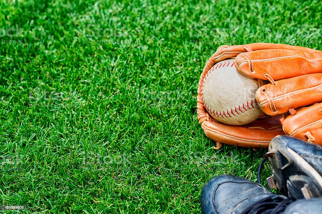 Old Softball in a glove with cleats in the grass stock photo