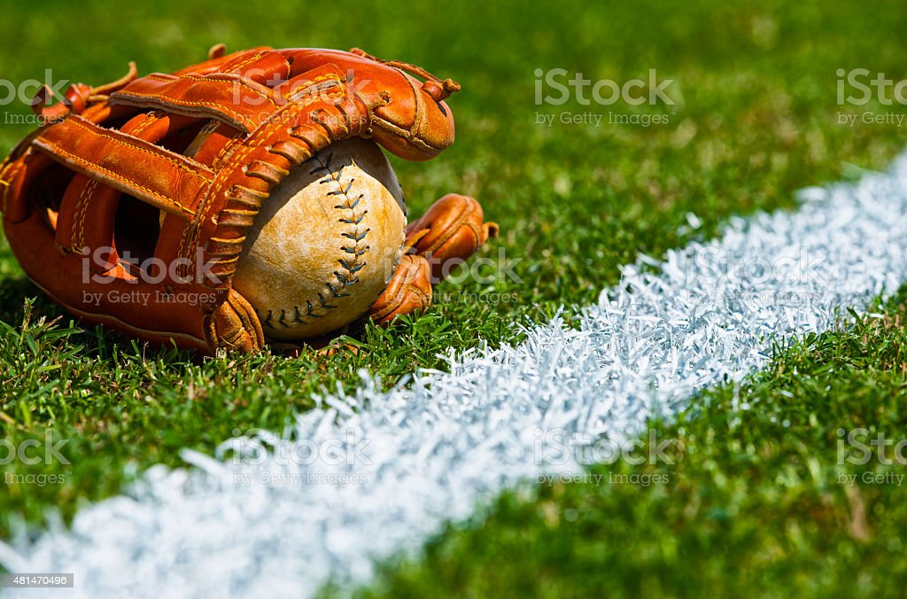 Old softball in glove on the outfield grass next to the foul line