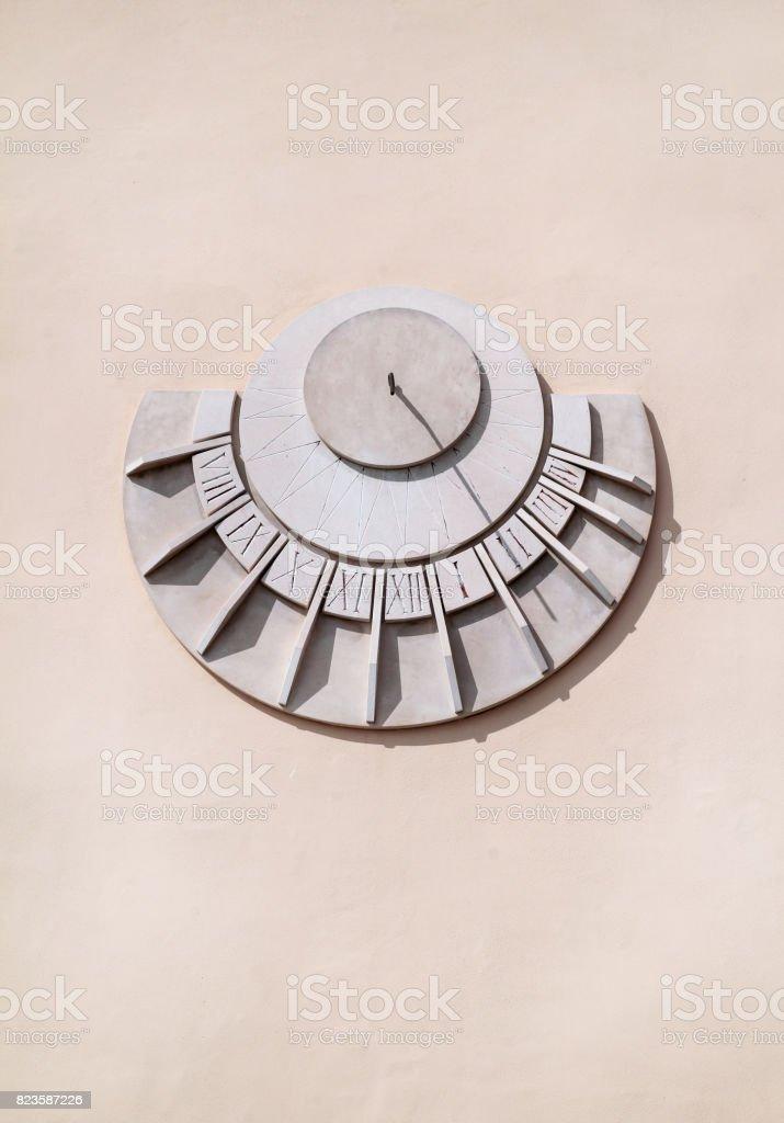 Antigo relógio solar em uma parede branca, close-up. À moda antiga dial de sol em uma parede de pedra isolada no branco, detalhe de um marcador de tempo solar antigo. Relógio de sol e parede gnômico antigo histórico decoração medieval. - foto de acervo